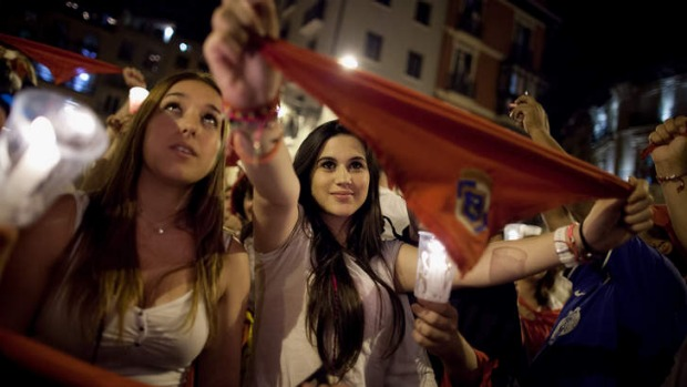 Revellers raise their scarves and candles as they sing the 'Pobre de Mi' song, marking the end of the San Fermin festival.