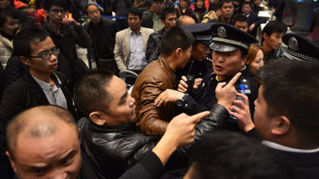 Stranded travellers arguing with police and airline personnel at Changshui International Airport in Kunming, after ...