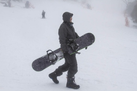 A snow boarding enthusiast heads for the slopes at Mount Baw Baw's Alpine Resort.