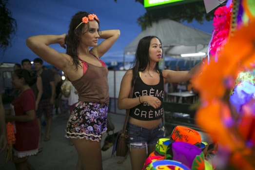 Women shop for headbands as they arrive for the full moon party.