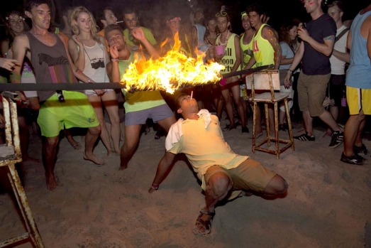 A man tries to light his cigarette walking underneath a burning rod during a limbo dance at the full moon party on the ...