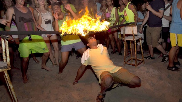 A man tries to light his cigarette walking underneath a burning rod during a limbo dance at the full moon party on the beach of Haad Rin.