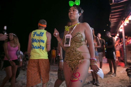 A Japanese woman dressed in costume attends the full moon party on the beach of Haad Rin.
