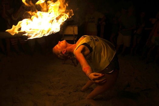 A woman walks underneath a burning rod during a limbo dance at the full moon party.