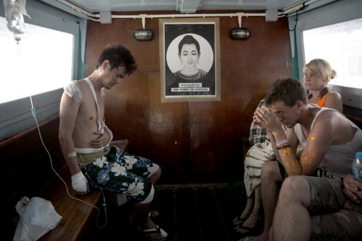 A Thai man (L) badly injured from a motorcycle accident gets transported to a Koh Samui hospital on a ferry leaving  Koh Phangan.
