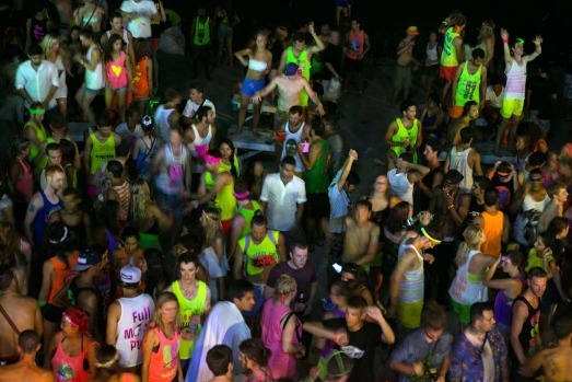 Hundreds of full moon partiers dance the night away on the beach of Haad Rin.
