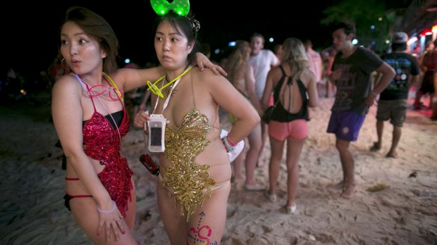 Japanese women dressed in costume attends the full moon party on the beach of Haad Rin.