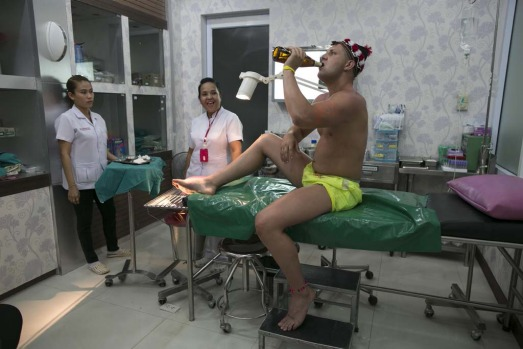 Jamie Harris from Scotland  drinks a beer before getting treated for his injured foot at the Bandon International clinic in Koh Phangan, Thailand.