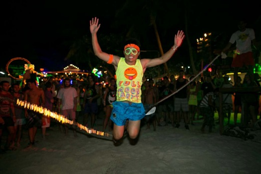 A man jumps over a burning rope at the full moon party.