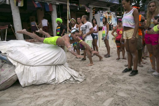 A man flies off a mattress coming down a water slide after sunrise at the full moon party.