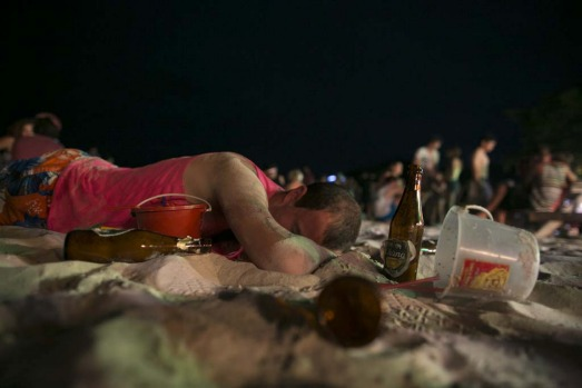 A man sleeps on the beach just before sunrise at the Full Moon party on Haad Rin beach.