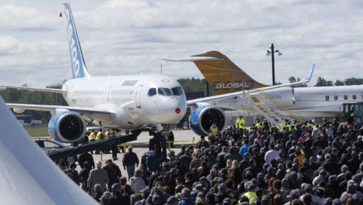 Bombardier employees gather near the new Bombardier CSseries aircraft in Mirabel, Quebec after its maiden flight.