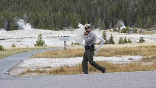 "Scaling back: A park ranger sets up a ""closed"" sign along the Upper Geyser Basin hiking area."