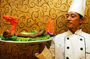 A cook poses with a plate of yak penis at the Guolizhuang Penis Restaurant in Beijing, China.