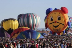 Hot air balloons, one of them shaped like a clock, are prepared before taking flight during the 42nd annual Albuquerque ...