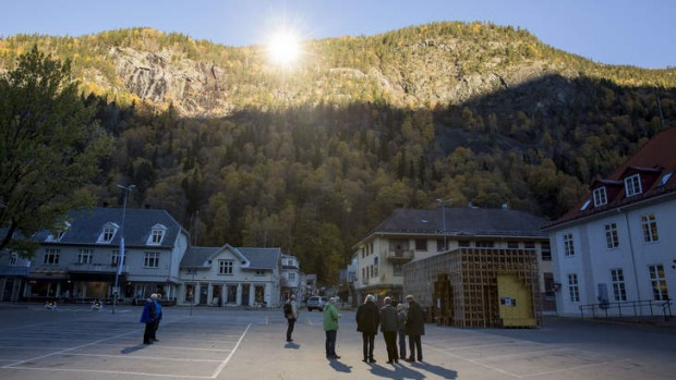 People gather on a spot in front of the town hall of Rjukan, Norway, where sunshine is reflected by three giant mirrors ...