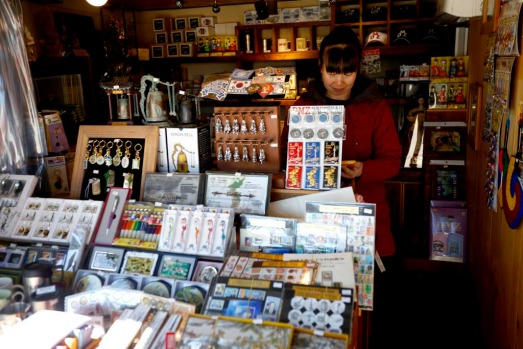 A shopkeeper uses her mobile phone at her souvenir shop at the Imjingak pavilion near the demilitarized zone which ...