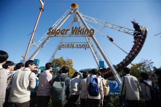 South Korean high school students look at the Super Viking ride at an amusement park in the Imjingak pavilion near the ...