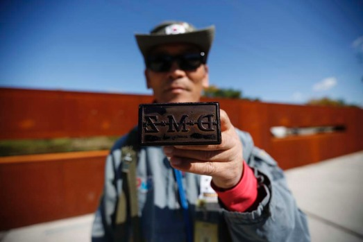A tour guide poses for photographs with a stamp for tourists at the Imjingak pavilion near the demilitarized zone which ...