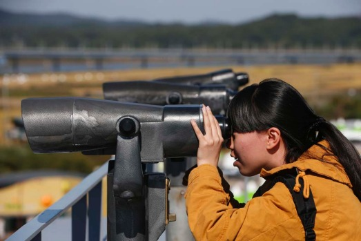 A Chinese tourist looks towards the north through a pair of binoculars at the Imjingak pavilion near the demilitarized ...
