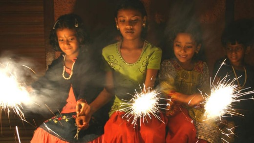 Three young Hindu girls celebrate Diwali with sparklers, India. DO NOT ARCHIVE