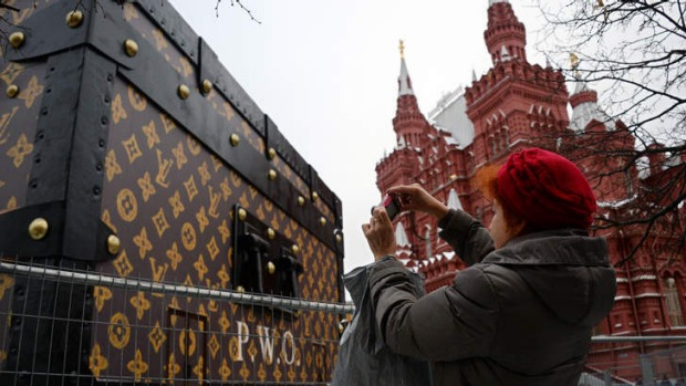 A woman takes photo of a giant Louis Vuitton trunk on Red Square in Moscow.