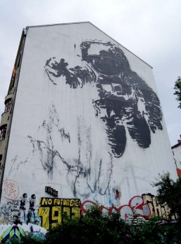 A giant astronaut covers a building wall in Berlin, created by artist Victor Ash.