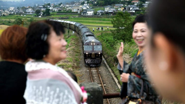 Passengers pose above the Nanatsuboshi, or Seven Stars, sleeper train