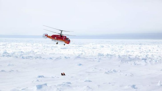 A helicopter from the Chinese icebreaker Xue Long hovers over an ice floe near the Australian icebreaker Aurora ...