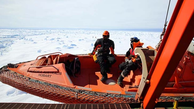 Rescuers aboard the Australian icebreaker Aurora Australis are lowered on a rescue boat to an ice floe next to the ship ...