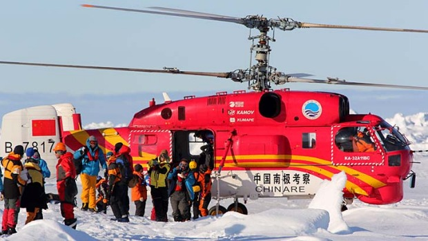 Researchers and passenegers leave the Chinese rescue helicopter after being evacuated from the ship Akademik Shokalskiy ...