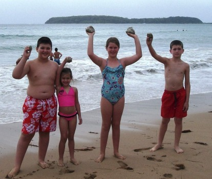 The Kylie family hold up chunks of pumice stone found on Broulee Beach.