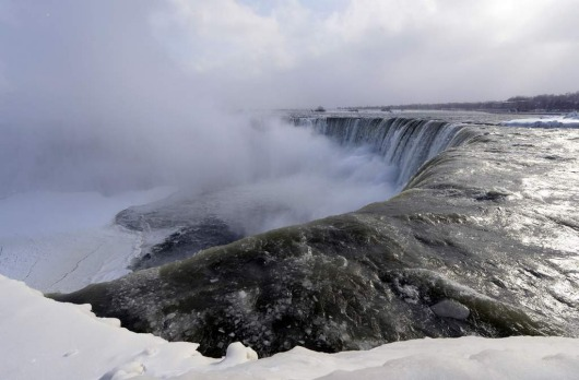 "Ice chunks and water flow over the falls Niagara Falls, Ontario. The frigid air and ""polar vortex"" that affected about ..."