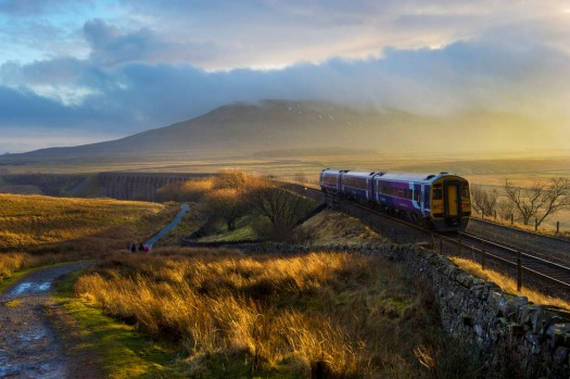 A train approaches Ribblehead Viaduct on the Settle to Carlisle Railway line, on a winter afternoon in North Yorkshire in the UK.