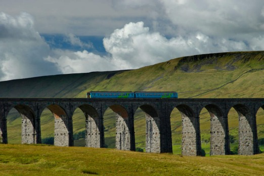 A passenger train crosses the Ribblehead Railway Viaduct.