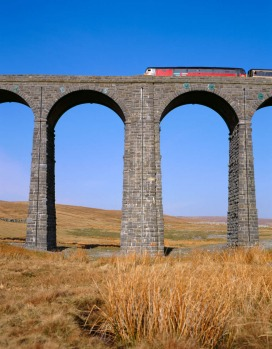 A train crosses the Ribblehead Viaduct on the Settle-Carlisle Railway, in North Yorkshire, England.