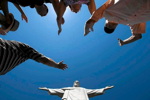 Visitors raise their arms to pray below the Christ Redeemer statue in Rio de Janeiro, Brazil.