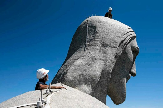 Repair workers examine the Christ Redeemer statue in Rio de Janeiro, Brazil.