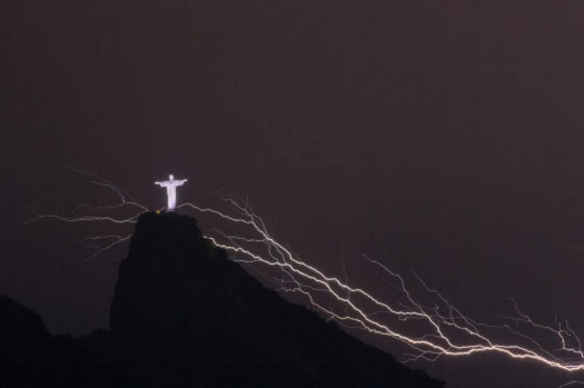 Lightning flashes over the Christ the Redeemer statue on top of Corcovado Hill in Rio de Janeiro on January 14, 2014.