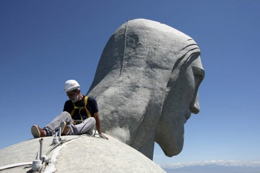 A worker inspects the Christ the Redeemer statue which was damaged during lightning storms in Rio de Janeiro.