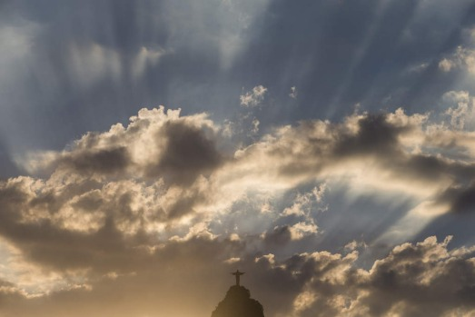 Christ the Redeemer statue is silhouetted against an early evening sky as the sun sets in Rio de Janeiro.