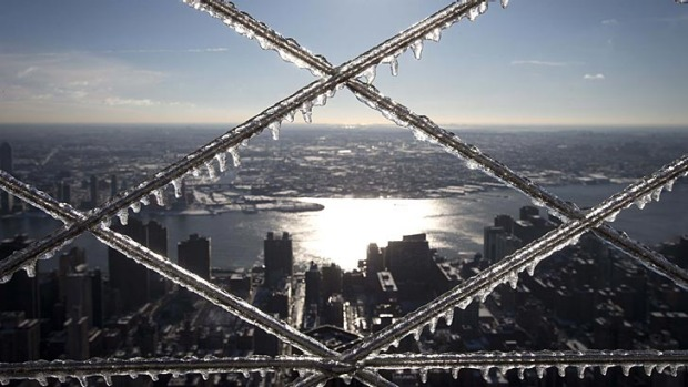 Sun shines through icicles that have formed on the grates of a fence on the roof of the Empire State Building in Manhattan.