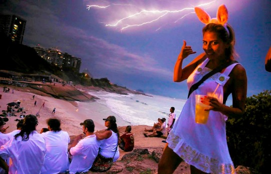 Reveller Daniela Solares from Bolivia walks past the camera as lightning strikes over Copacabana Beach during the Vem Ni ...