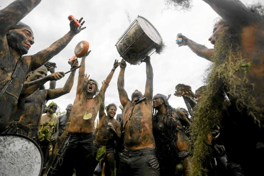 Mud-covered revellers dance and sing at the 'Bloco da Lama' beneath an overcast sky in Paraty, Brazil.