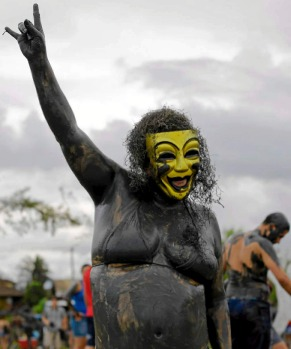 A mud-covered reveller poses for a photo during the mud street party? in Paraty, Brazil. The ?Bloco da Lama? was founded ...