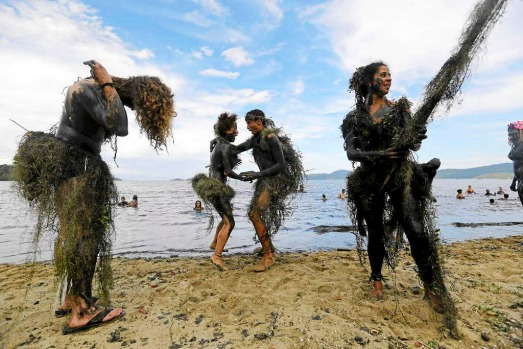 Mud-covered revellers dance during the mud street party in Paraty, Brazil. Fans of the 'Bloco da Lama' insist the event ...