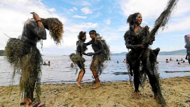 Mud-covered revellers dance during the mud street party in Paraty, Brazil. Fans of the 'Bloco da Lama' insist the event is among the most democratic of the thousands of booze-filled parties that take over Brazilian streets throughout Carnival, because revellers do not need to buy costumes, but instead create a disguise by smearing handfuls of mud on their bodies, some adding a crown and/or a skirt of swampy vines.