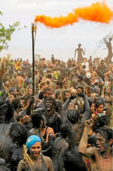 Gangs of mud-covered revellers dance during the mud street party? in Paraty, Brazil.