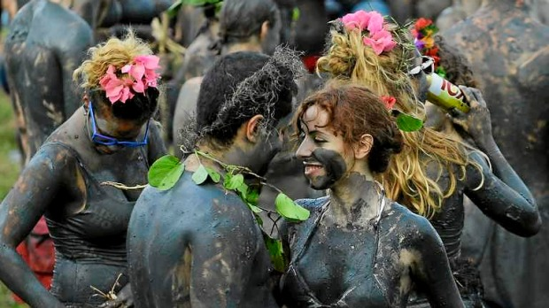 Mud-covered revellers dance during the mud street party? in Paraty, Brazil.