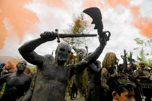 Mud-covered revellers attend the mud street party underneath a hazy sky and orange smoke caused by smoke bombs, in ...